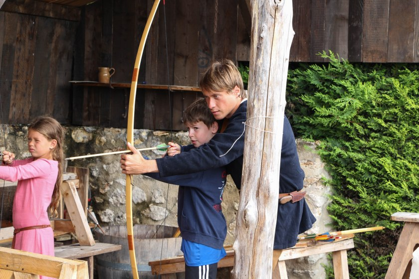 Oli learning to fire his bow + arrow. The little girl beside him was a total sharp shooter!
