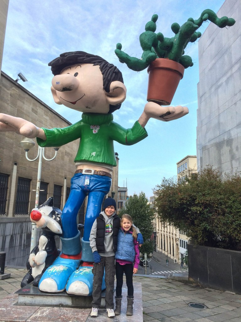 The kids with Gaston, a Belgian comic strip character, at the top of the path to the Comic Strip Museum.