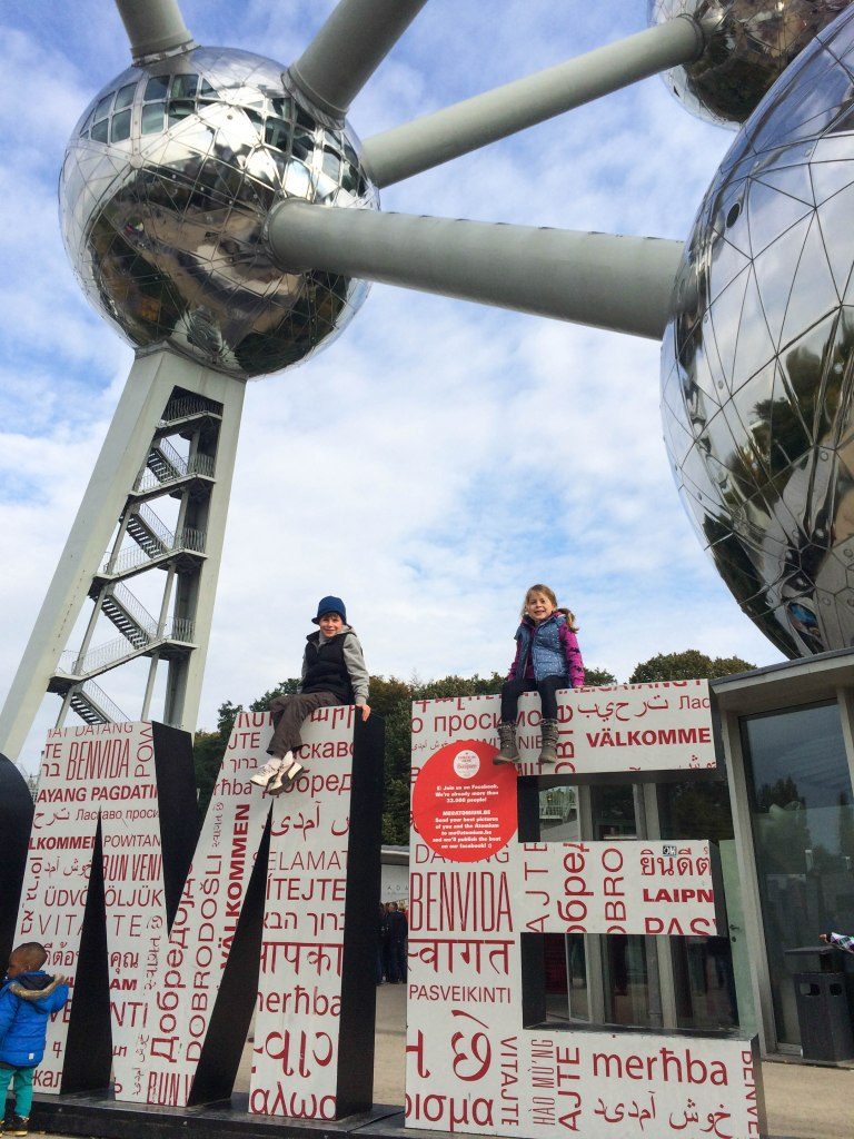 The kids at the end of the giant Welcome sign, in front of the Atomium.